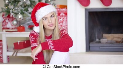 Pretty young woman sitting on the floor with christmas tree...