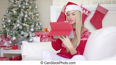 Pretty blond young woman sitting on couch with touchpad...
