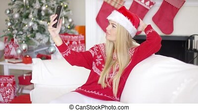 Sexy blond girl in Christmas outfin taking a selfie with her...