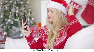 Young happy blond girl in Christmas outfit using mobile...