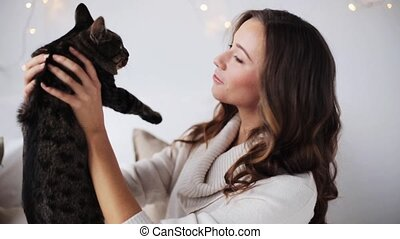 young woman playing with cat at home - pets and people...