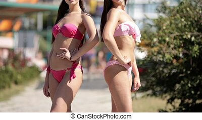 Two girls in pink swimsuits and sunglasses posing in the...