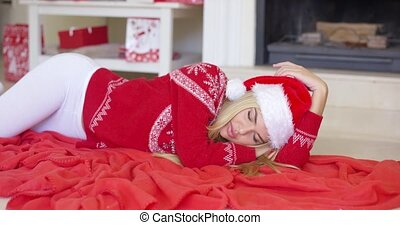 Adorable girl in Christmas outfit lying on the floor with...