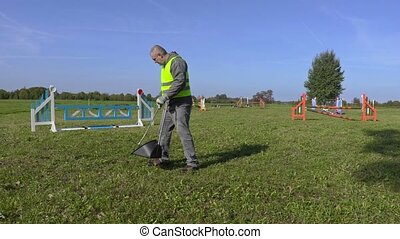 Horse handler maintaining hurdle field
