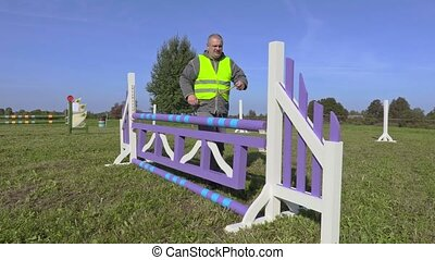 Horse handler with measure tape near hurdle