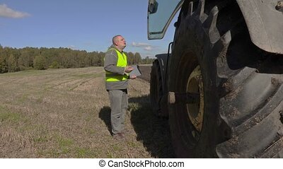 Angry farmer talking near to the tractor