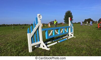 Horse handler writing near hurdle