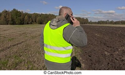 Farmer talking on the phone and go to the tractor