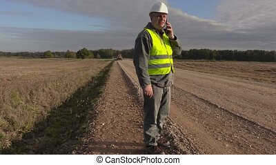 Road construction engineer talking on phone