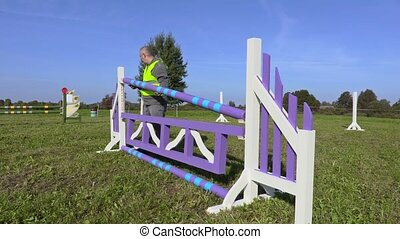 Horse handler try to fix hurdle