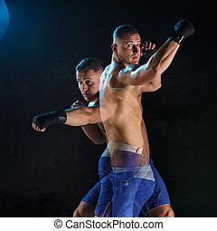 Male boxer boxing in a dark studio - Male Athlete boxer...