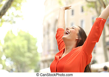 Excited woman raising arms in the street