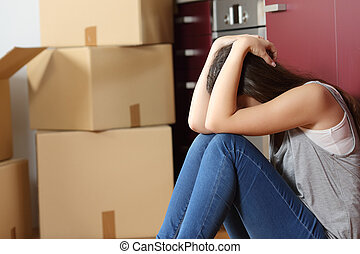 Sad evicted woman worried moving house sitting on the floor...