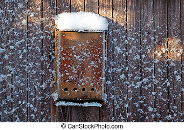 old Mail box on a fence filled up by snow