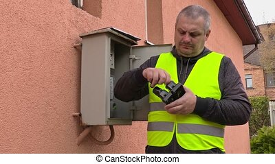 Electrician checking fuse box near house