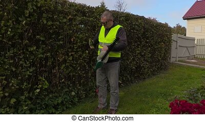 Landscaping worker talking on phone and doing hedge trimmer...
