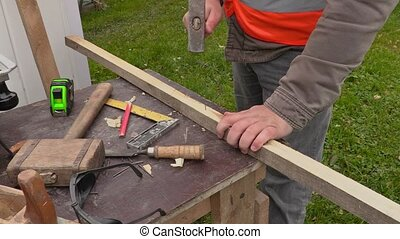 Carpenter with hammer and nail at the working table