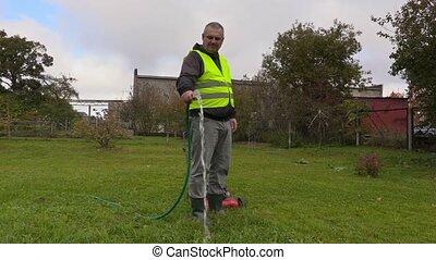 Man watering in garden near lawnmower
