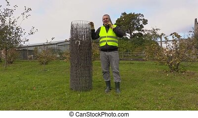 Man with wire fence in the garden