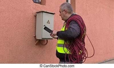 Electrician talking on phone and open fusebox near house