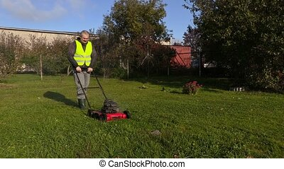 Worker pushing lawnmower and remove stone from lawn
