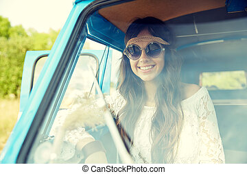 smiling young hippie woman in minivan car - summer holidays,...