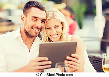 happy couple with tablet pc at restaurant lounge - love,...