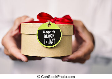 man with a gift box with the text black friday - closeup of...