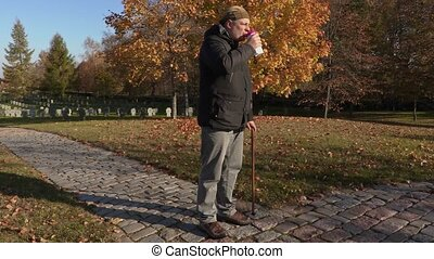 Disabled man with cane and coffee on path in cemetery