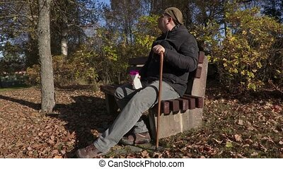 Disabled man sitting on the bench and drinking coffee