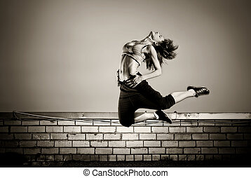 black and white photo of girl jumping on the roof