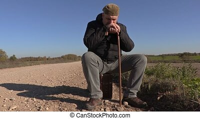 Lonely man with crutch sitting on suitcase on rural road