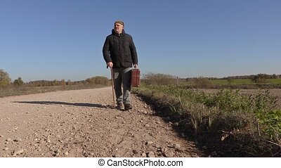 Disabled man with cane and suitcase on the road