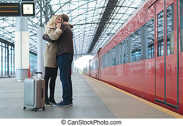 Relationship - Young embracing couple at the station