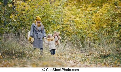 Little daughter with her mommy and Taddy bear walks in autumn park - plays the leaves