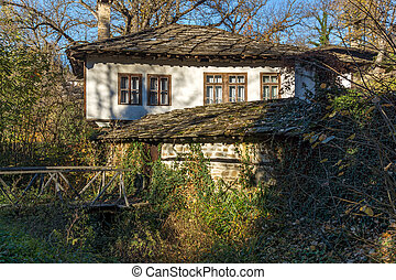 Autumn landscape with wooden Bridge and old house in village...