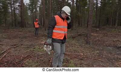 Lumberjack with chainsaw talking on phone in forest