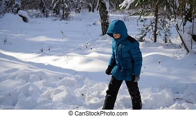 the child tumbles in the snow in the winter park