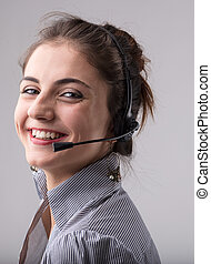 Smiling happy businesswoman wearing a headphone grinning as...