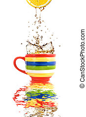 Lemon juice and splash of tea in color cup with reflection