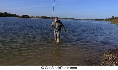 Man with bare feet and fishing rod in lake