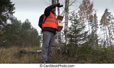 Ornithologist with binoculars and bird nesting box