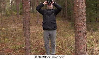 Man staring at the tree tops with binoculars