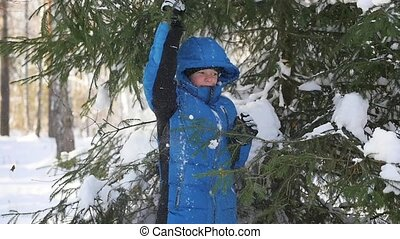 teen throws off snow from tree branches in a sunny day