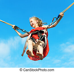 Little girl on bungee trampoline with cords. Place for text.