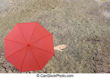 Red umbrella and a hand of man standing on soil dry pond and...
