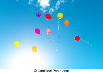Many colorful baloons in the blue sky.