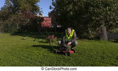 Worker starting lawn mower