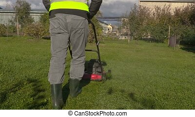 Man start using lawn mower in sunny day