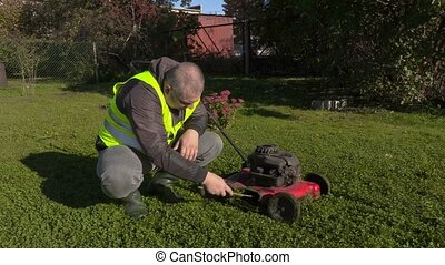 Worker cleaning lawnmower